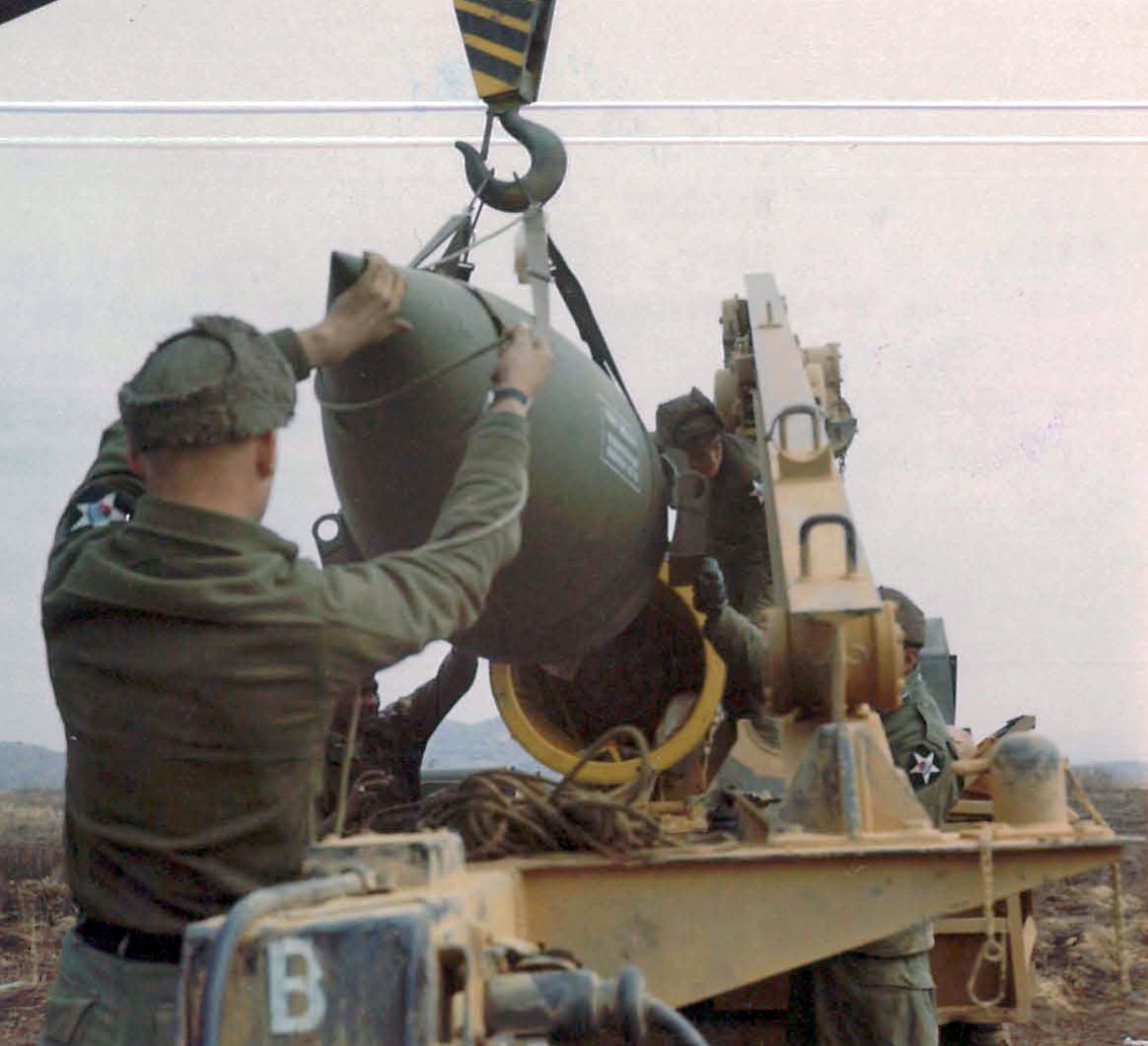 Members of the Headquarters Battery, 1st Battalion, 12th Artillery, 2nd Infantry Division hoisting the warhead section