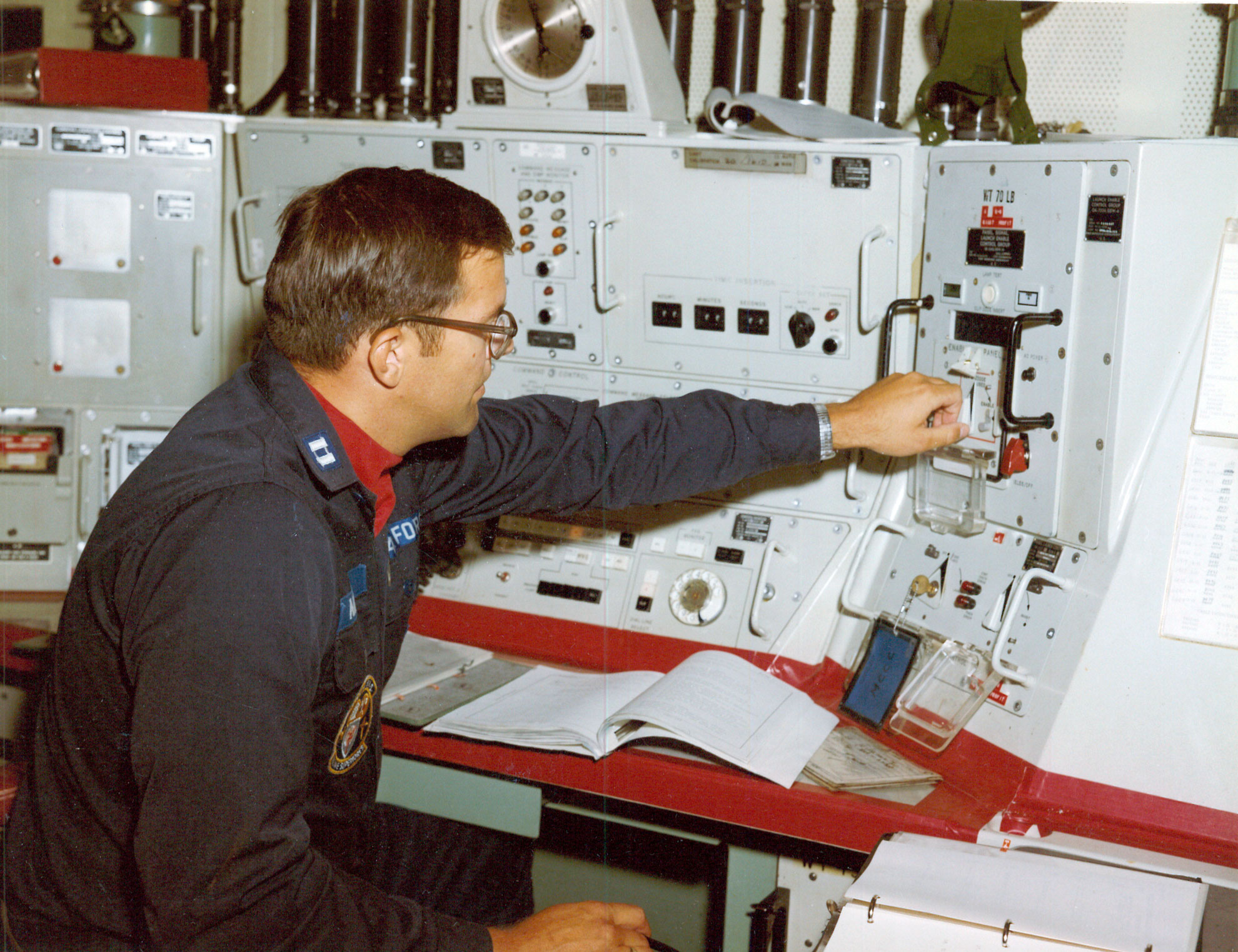 Launch control officer, seated at launch control panel, turns switch to start launching sequence. Testing operational readiness of Minuteman crews using Modified Operational Missiles