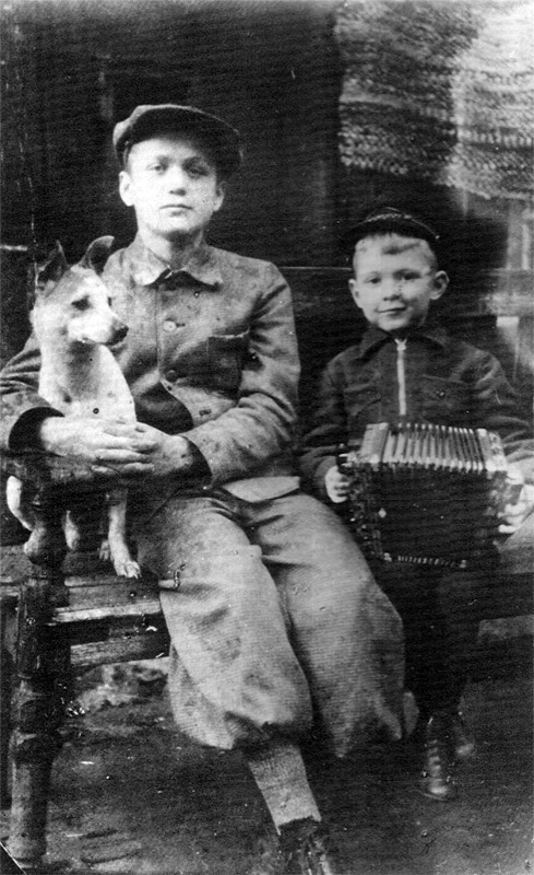 Young Yuri Orlov holding accordian with his cousin Vladimir and dog Jack.