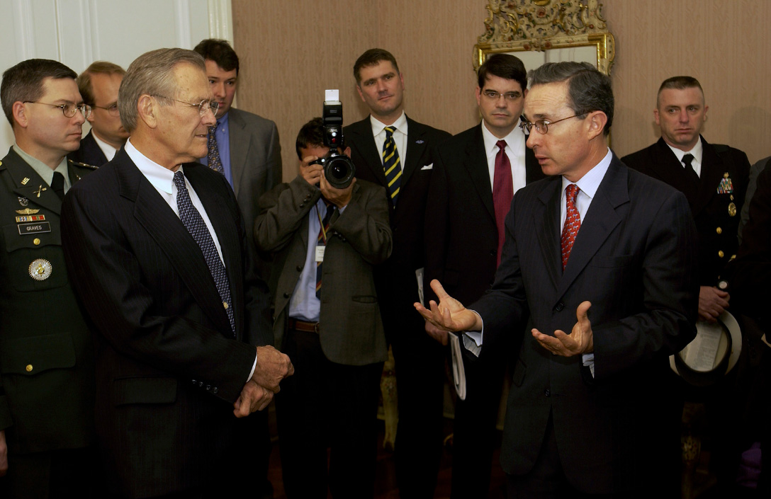 Defense Donald H. Rumsfeld (left) listens as President Álvaro Uribe (right)